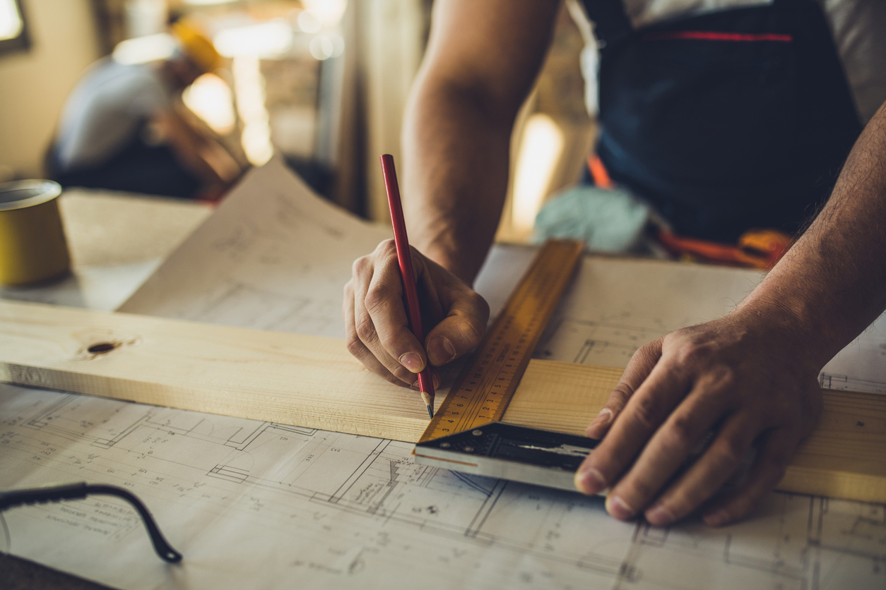 Close up of unrecognizable carpenter making measurements and drawing on a plank - Advantages of Modern Design a concept.